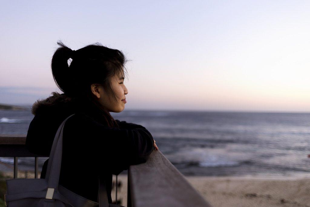 girl ponytail dock shore ocean beach